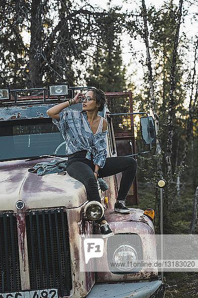 Junge Frau sitzt auf einem kaputten Lastwagen