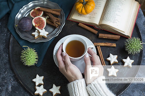 Frau trinkt im Herbst eine Tasse Tee  Teilansicht