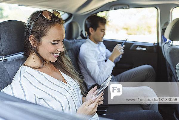 Frau und Mann benutzen Tablet und Handy auf dem Rücksitz eines Autos