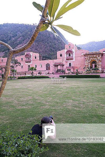 Indien  Rajasthan  Alwar  Touristin beim Fotografieren des Heritage Hotel Ram Bihari Palace