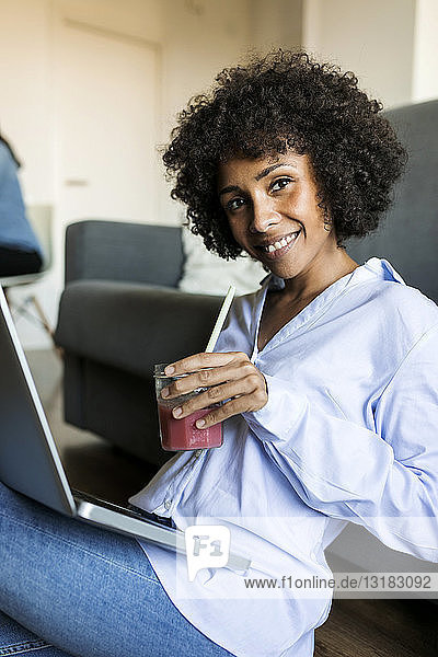 Portrait of smiling woman with soft drink sitting on floor using laptop