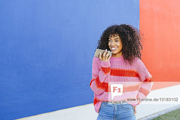 Porträt einer lächelnden jungen Frau  die mit einem Mobiltelefon eine Sprachnachricht sendet