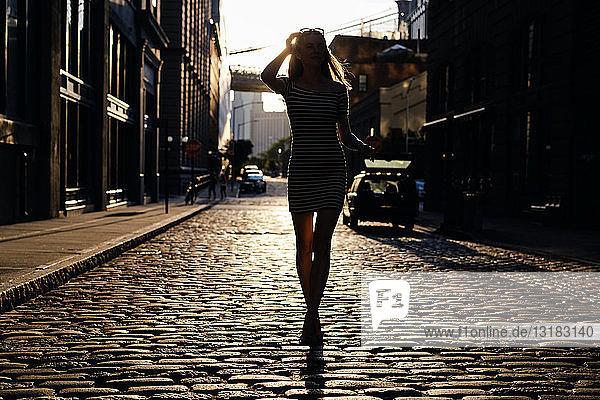 USA  New York  Brooklyn  Dumbo  Silhouette einer jungen Frau  die im Gegenlicht auf der Straße steht