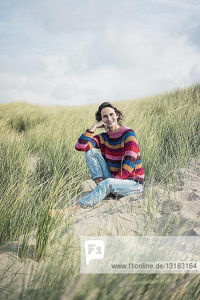 Reife Frau entspannt sich am Strand  sitzt in den Dünen