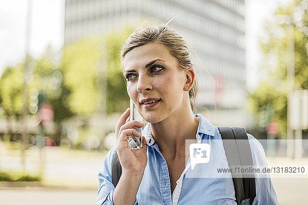 Porträt einer Frau mit Rucksack in der Stadt beim Telefonieren mit dem Handy