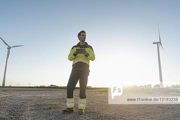 Ingenieur  der in ländlicher Landschaft an einem Windpark steht und ein Tablett hält