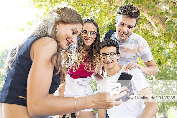 Eine Gruppe von Freunden im Park genießt die gemeinsame Zeit und schaut auf ein Handy