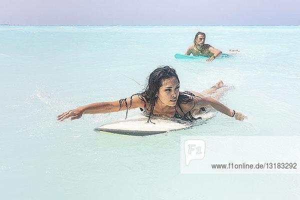 Junges Paar amüsiert sich auf dem Meer  beim Surfen