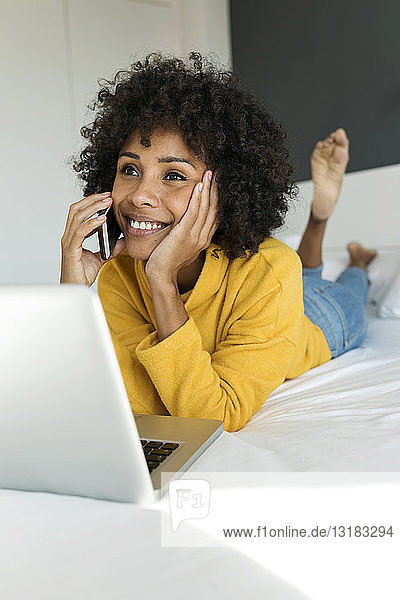 Smiling woman lying on bed talking on cell phone