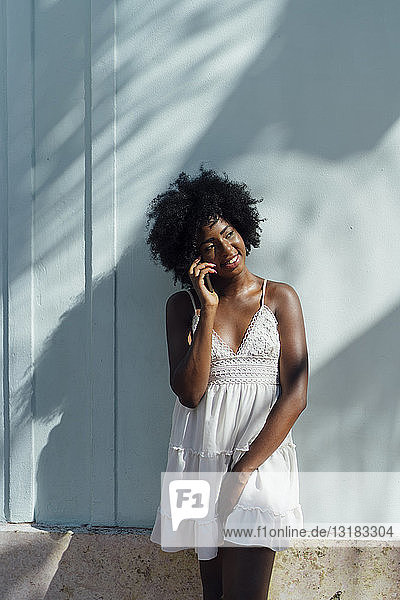 Smiling young woman wearing white dress talking on the phone at a wall