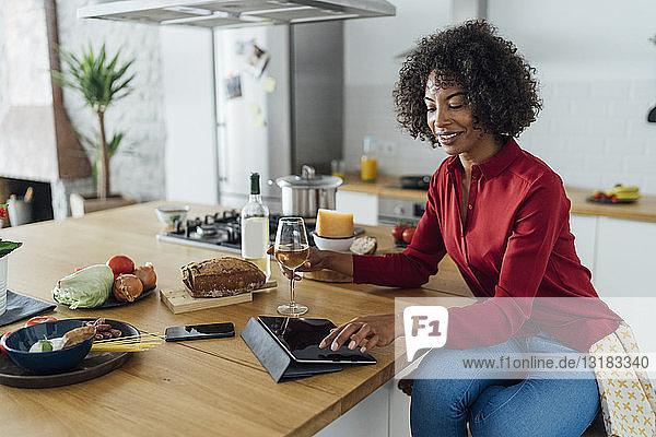 Frau sitzt in der Küche mit einem Glas Weißwein und benutzt ein digitales Tablett