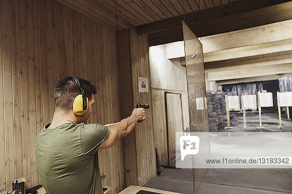 Man aiming with a pistol in an indoor shooting range