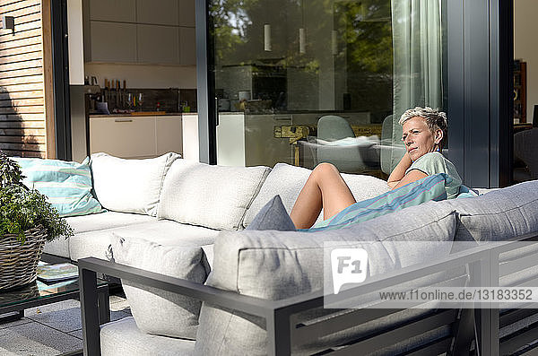 Pensive woman sitting on couch on terrace of her home