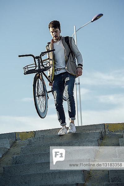 Junger Mann mit Pendler-Fixie-Fahrrad die Treppe hinunter