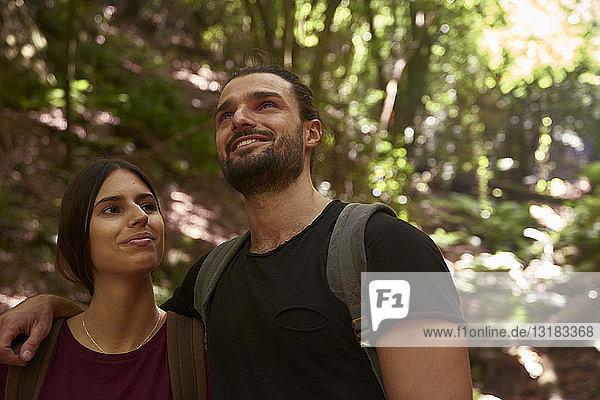 Spanien  Kanarische Inseln  La Palma  lächelndes Paar in einem Wald  das sich umsieht