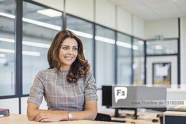 Lächelnder Büroangestellter am Schreibtisch sitzend