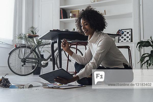 Disignerin  die auf dem Boden ihres Heimbüros sitzt und ein digitales Tablet benutzt