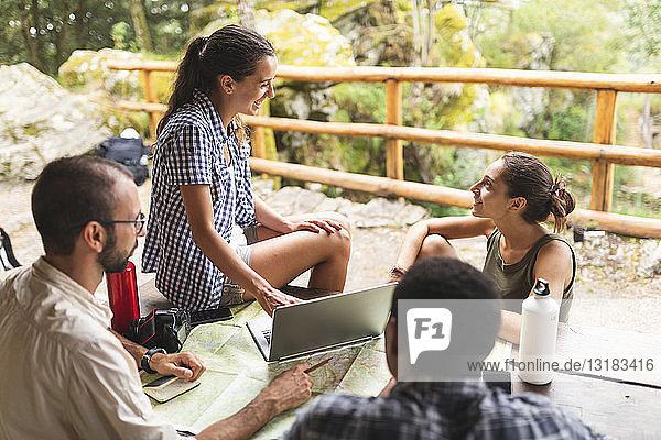 Gruppe von Wanderern  die zusammensitzen und eine Wanderroute mit Karte und Laptop planen