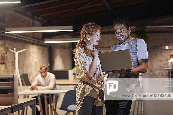 Mann im Büro hält Laptop in der Hand  spricht mit Kollege