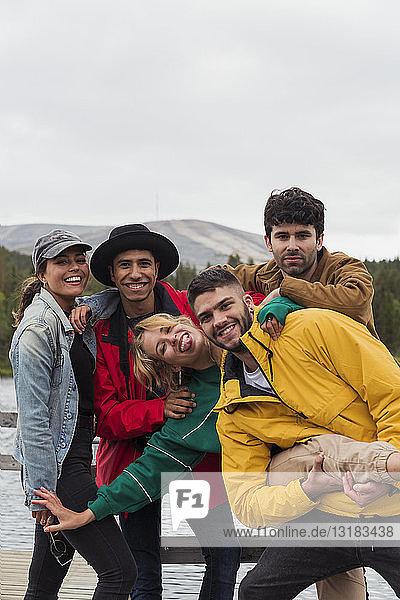 Finnland  Lappland  Porträt fröhlicher  verspielter Freunde auf einem Steg an einem See