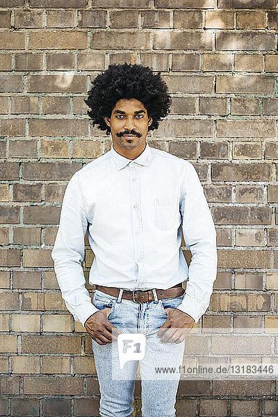 Mittelgroßer erwachsener Mann steht vor einer Ziegelmauer  Hände in den Taschen