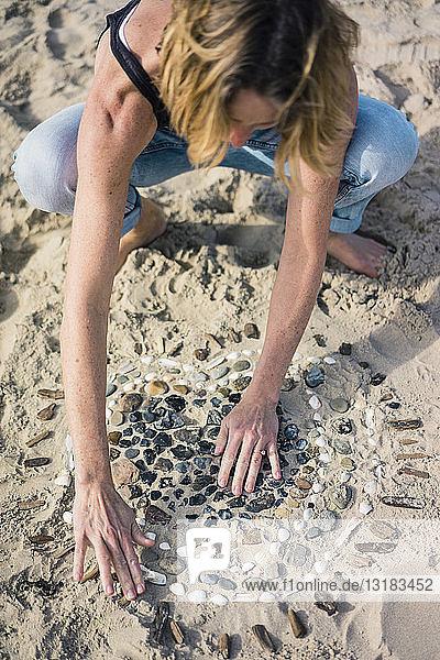 Reife Frau macht am Strand ein Herz aus Muscheln