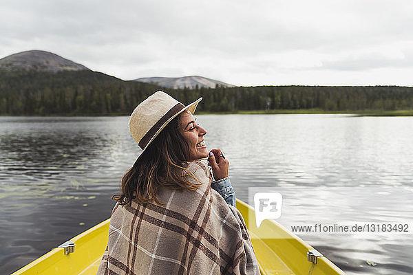 Finnland  Lappland  glückliche Frau mit Hut auf einem Boot auf einem See