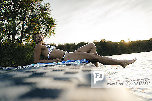 Frau im Bikini  die auf einem Schwimmer auf einem See liegt
