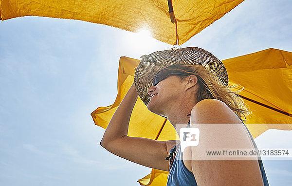Lächelnde Frau mit Strohhut unter Sonnenschirm im Sonnenlicht
