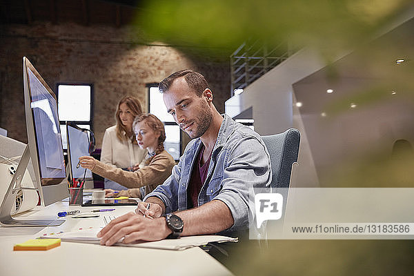 Man working at desk in office  smiling