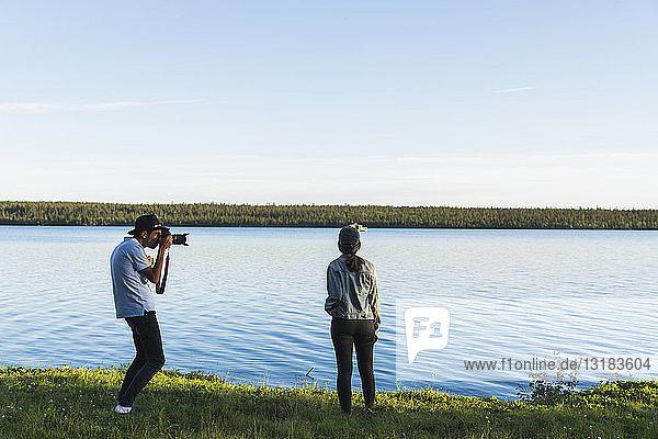 Junger Mann fotografiert junge Frau an einem See