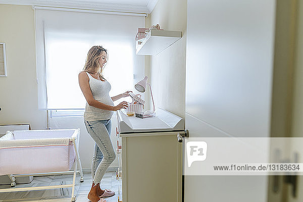 Pregnant woman preparing the baby room
