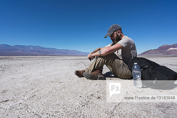 USA  California  Death Valley  man sitting on ground in the desert having a rest