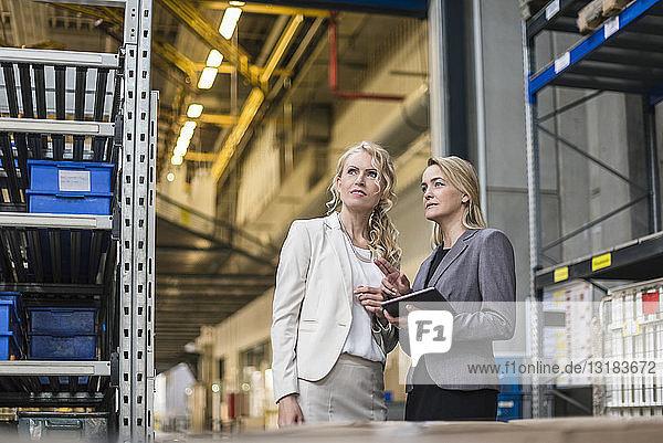 Zwei Frauen mit Tabletten im Fabriklager