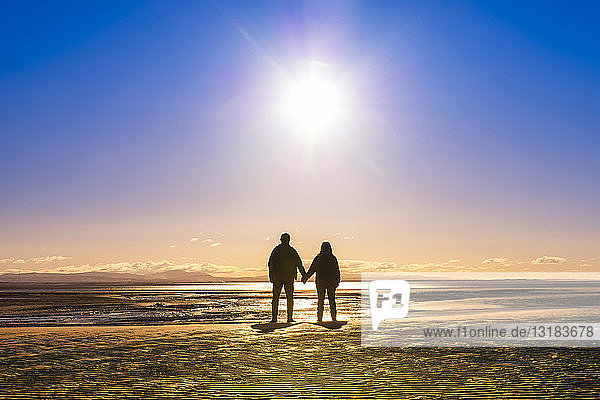 Great Britain  Scotland  Solway Firth  silhouette of mature couple  hand in hand