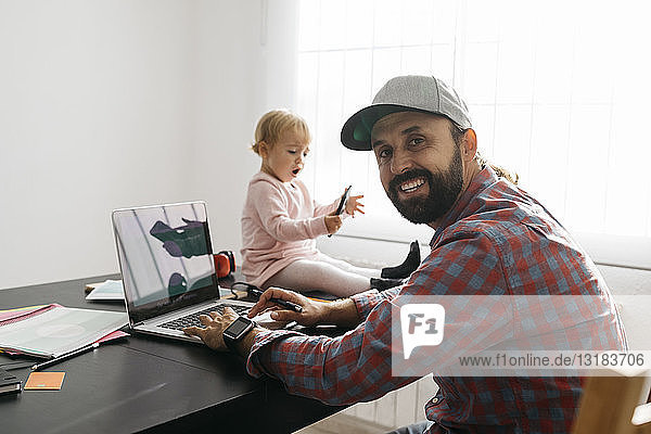 Father working from home  using laptop with his gaughter sitting on the desk  playing