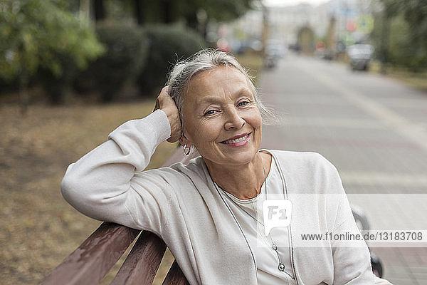 Porträt einer lächelnden älteren Frau  die sich auf einer Bank entspannt