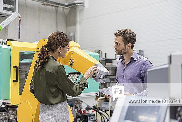 Geschäftsmann und -frau bei einem Treffen vor Industrierobotern in einem High-Tech-Unternehmen