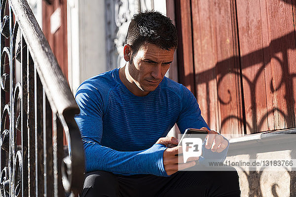 Athlete sitting on front stoop using cell phone