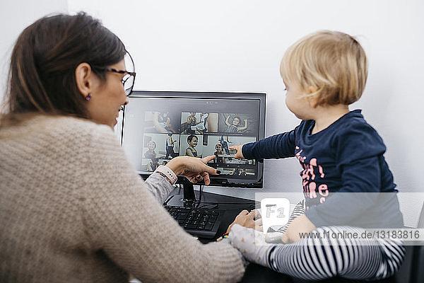 Mutter mit kleiner Tochter sitzt am Schreibtisch und schaut auf den Computerbildschirm