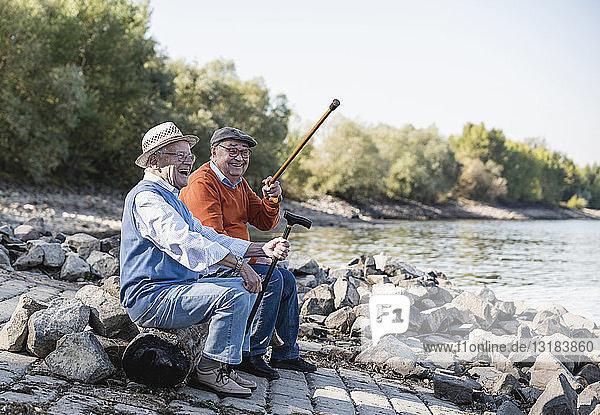 Zwei alte Freunde sitzen am Flussufer und amüsieren sich