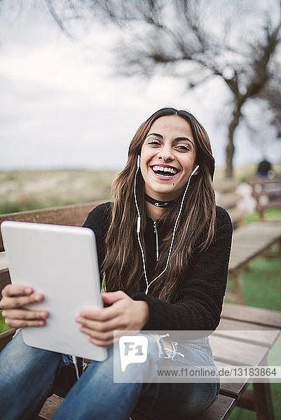 Porträt einer lachenden jungen Frau  die mit Tablett und Kopfhörer auf einer Bank im Freien sitzt