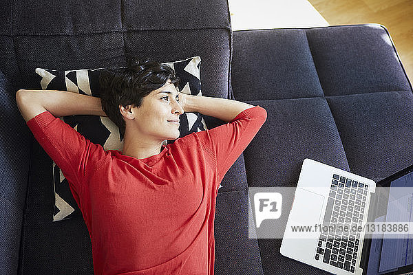Woman lying on couch at home next to laptop