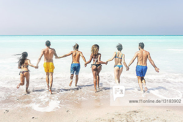 Gruppe von Freunden am Strand  rennt ins Meer und hält sich an den Händen
