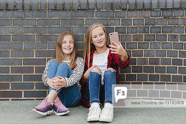 Porträt von zwei lächelnden Mädchen  die vor einer Backsteinmauer sitzen und sich mit einem Smartphone selbstständig machen
