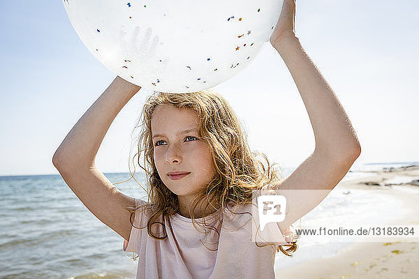 Girl holding a balloon at the beach