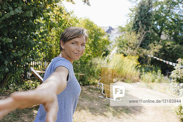 Porträt einer lächelnden Frau im Garten  die die Hand ausstreckt