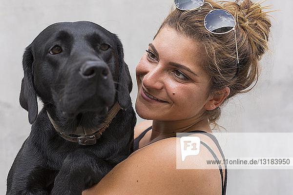 Porträt einer glücklichen jungen Frau mit ihrem schwarzen Hund