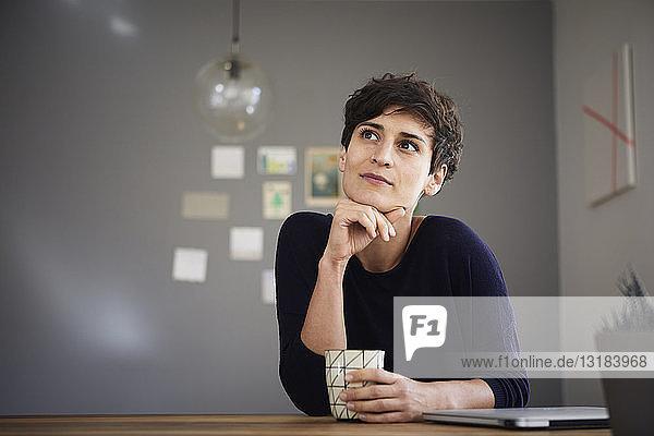Porträt einer Frau zu Hause am Tisch sitzend bei einer Tasse Kaffee