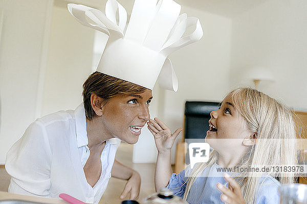 Glückliche Mutter und Tochter spielen zu Hause und setzen die Kochmütze auf
